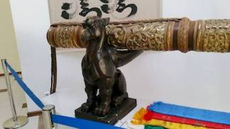 Carving of mythical creature on pipe