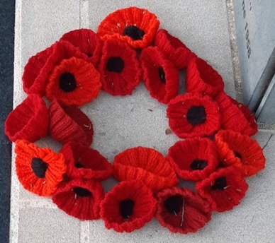 knitted poppy wreath by statue